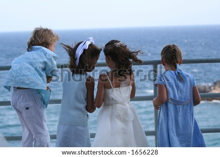 four children playing and admiring a beautiful sea view.