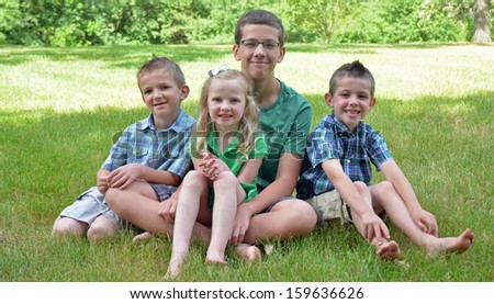 four children posing nicely in the grass - stock photo