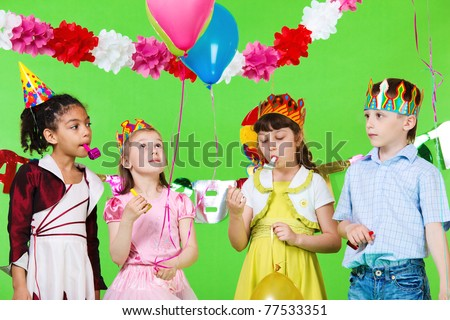Four children with noisemakers and balloons - stock photo