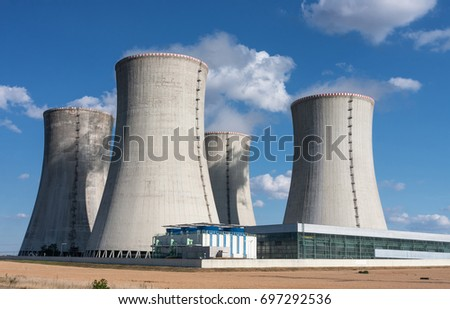 Four  chimneys of nuclear power station in the summer day, cooling towers of nuclear plant against blue sky.