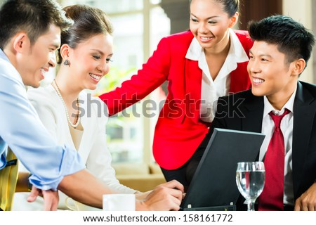Four Chinese Asian business men and women having meeting in a hotel lobby looking at documents on laptop and drinking coffee - stock photo