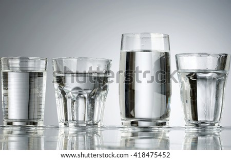 Four classic glasses with water and water drops - stock photo