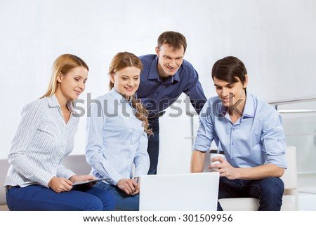 Four co-workers discussing business ideas in office