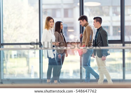Four colleagues meet in the hallway office building