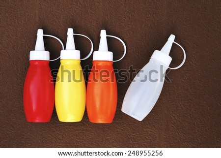 Four color of plastic sauce bottles are on the brown paper background - stock photo