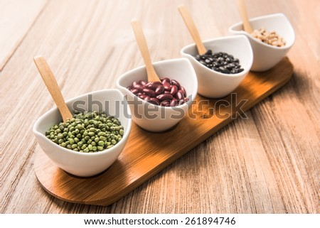 four colored beans  in ceramic bowl selective focus is greenbeans - stock photo
