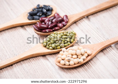 four colored beans in wooden spoon.selective focus is Green mung beans - stock photo