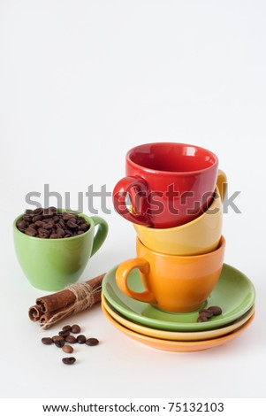 Four colorful cups with fragrant coffee beans and cinnamon sticks