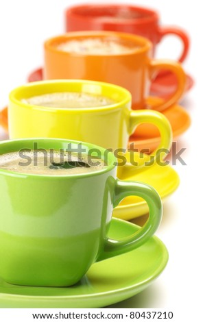 Four colorful cups with fresh coffee on white background. - stock photo