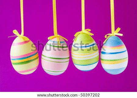four colorful easter eggs isolated on purple background