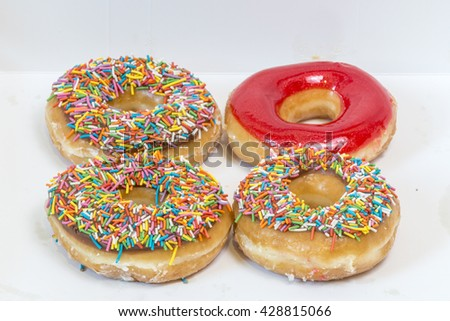 Four colorful glazed donuts isolated on a white background