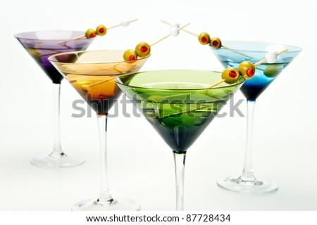 Four colorful martini glasses shot in the studio on white. - stock photo