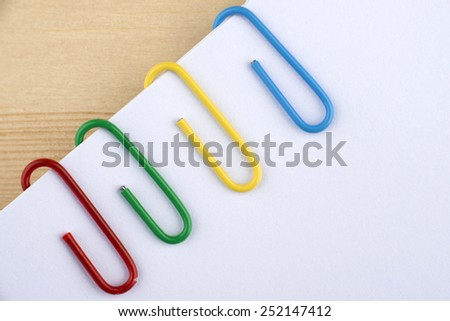 Four colorful paper clips in macro on the white paper - stock photo