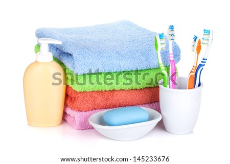 Four colorful toothbrushes, soap and towels. Isolated on white background