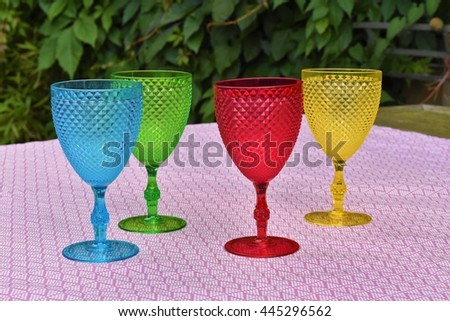 Four colorful wine glasses on a garden table