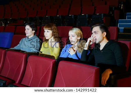 Four concentrated people watch movie in movie theater. Focus on right girl.