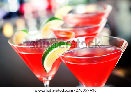 Four Cosmopolitan cocktails shot on a bar counter in a nightclub - stock photo