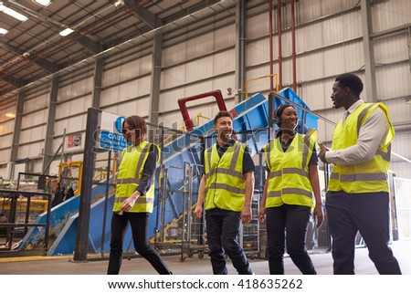 Four coworkers talk as they walk in an industrial interior - stock photo
