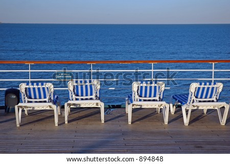 Four Cruise Chairs on the deck - stock photo