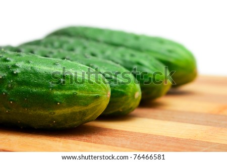 Four cucumbers with pimples on kitchen board isolated on white - stock photo