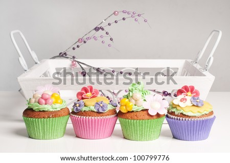 Four cupcakes in a row in front of a dinner tray - stock photo