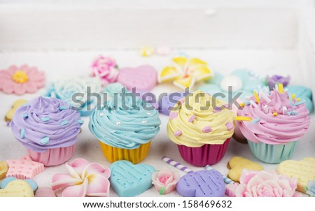 four cupcakes with flower and heart decoration - stock photo