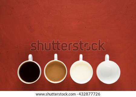 Four cups on a red background. One is with black coffe, one is with coffee and milk, one is with milk only and the last is empty.