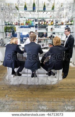 four customers and a barkeeper sitting, standing, talking and drinking at a bar - stock photo