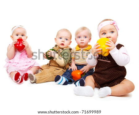 Four cute babies group holding large peppers in hands - stock photo