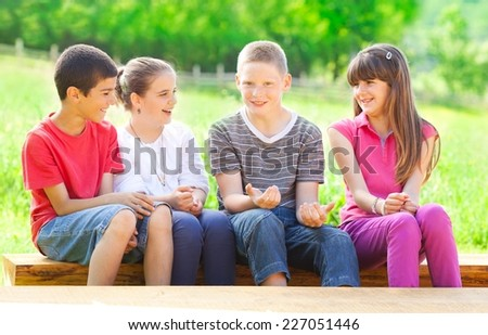 Four cute school children sitting in the park and laughing. Elementary age.