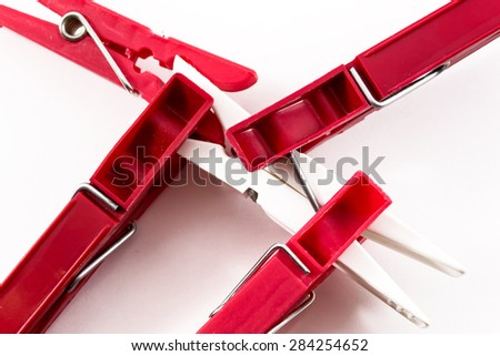 Four dark red plastic pegs overcoming a single solitary white plastic peg - stock photo