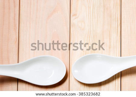 Four decorate white spoon from top view with pain wood background. Close up focus with shallow depth of field. - stock photo