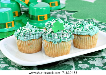 Four decorated cupcakes in a festive St. Patrick's day setting with shamrocks and fedoras. - stock photo