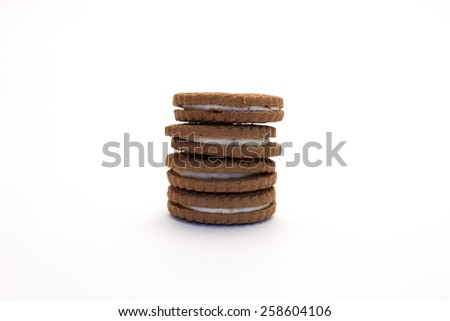 Four delicious crunchy chocolate and vanilla cream cookies set in a pile in white background