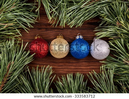 Four different colored Christmas balls surrounded by pine branches top view - stock photo