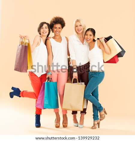 Four different women sharing the passion for shopping. - stock photo