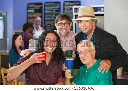 Four diverse adults smiling with coffee mugs - stock photo