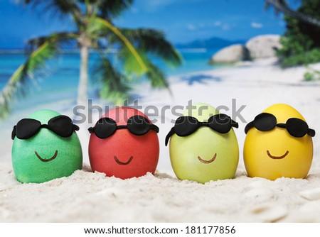 Four easter eggs with sunglasses on ocean beach  - stock photo