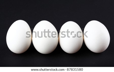 Four eggs isolated on black background