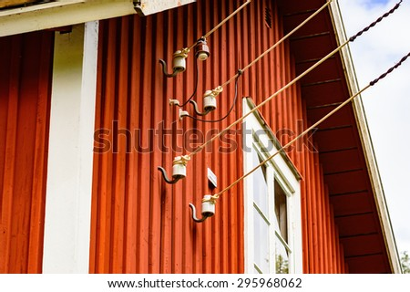 Four electric wires attached to red wooden building beside window. Small white warning sign beside wires. - stock photo