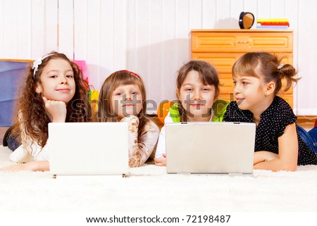 Four elementary aged girls lying in front of laptops - stock photo