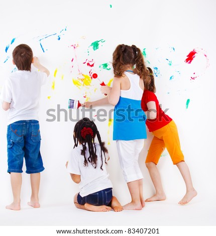 Four elementary aged kids painting  wall - stock photo
