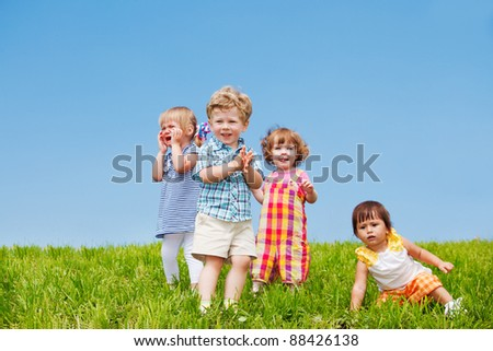 Four emotional toddlers on green grass - stock photo