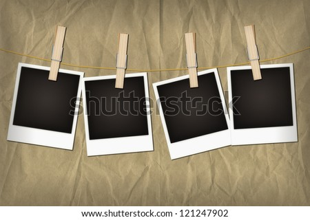Four empty old-fashioned instant photos pegged to a clothesline, on grunge brown paper background. Space for insertion of your own image or text.