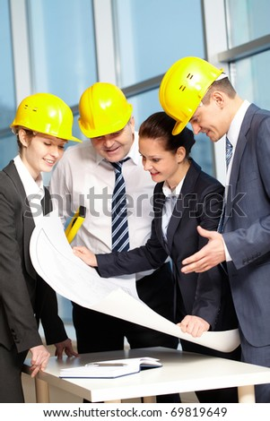 Four engineers standing at table and discussing a project - stock photo