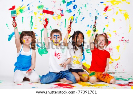 Four excited preschool friends painting - stock photo