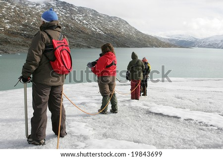 four explorers in a glacier - stock photo