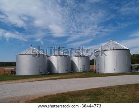 Four farm silos beside a country rock road in front of  ripening soybean field with plenty of copy space. - stock photo