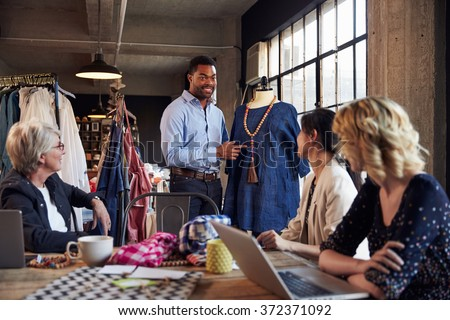 Four Fashion Designers In Meeting Discussing Garment - stock photo
