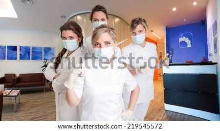 Four female dentists posing with masks and equipment - stock photo